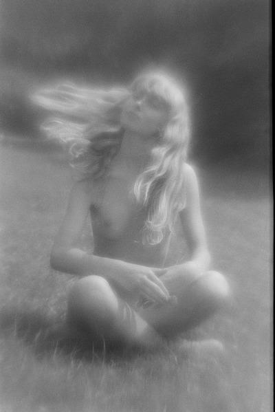 Čičmany. Akt-Pleinair 1980. Auf einer Wiese sitzende junge Frau mit wehenden langen blonden Haaren