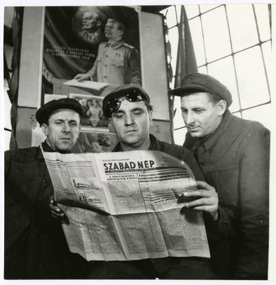 Államosítás. Három munkás Szabad Népet olvas, háttérben Sztálin és Lenin portréja.