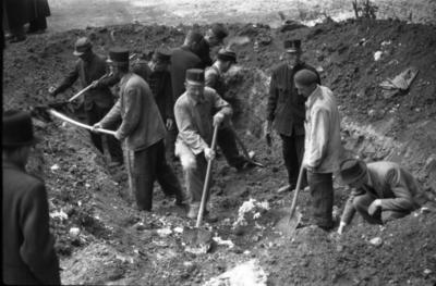 A Budai Chevra Kadisa Maros utcai kórházában 1945. január 12-én elkövetett nyilas tömeggyilkosság áldozatainak exhumálása a kórház udvarán. Kihantolják a holttesteket.