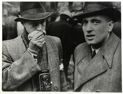 A Budai Chevra Kadisa Maros utcai kórházában 1945. január 12-én elkövetett nyilas tömeggyilkosság áldozatainak exhumálása a kórház udvarán. Kohn István (jobbra) volt munkaszolgálatos, az egyik koronatanú, aki az áldozatokat elföldeltette. Mellette egy fényképész, nyakában Rolleiflex fényképezőgép.