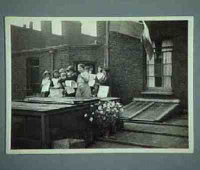 Series of 8 pictures Hoisting the colours at 400 Old Ford Road Sylvia Pankhurst pointing at the camera The little boy is the grandson of George Lansbury
