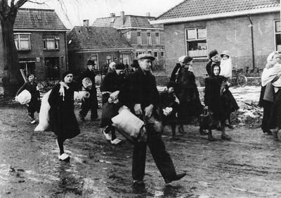 Bepakt en bezakt komen de Scheveningse evacués aan bij de fabriek in de Dijkstraat waar de kustbewoners in de kantine worden ontvangen op 12 januari 1943. Uit het boek Aalten in Oorlogstijd van J.G. ter Horst
