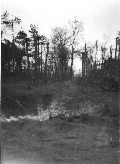 Bomkrater met op de achtergrond de woning van de familie Ten Barge die bij zware luchtgevechten op 26 maart 1943 geheel uitbrandde. Uit het boek Aalten in Oorlogstijd van J.G. ter Horst
