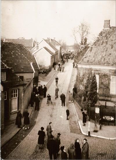 Gespannen staan bewoners uit de omgeving van de Berkenhovestraat bijeen op de morgen van zondag 30 januari 1944. Op de achtergrond is de overvalwagen te zien die voor de Christelijk Gereformeerde kerk staat. Een zestal jongelui werd na afloop van de kerkdienst gearresteerd. Uit het boek Aalten in Oorlogstijd van J.G. ter Horst