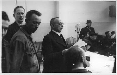 Burgemeester A.J.W. Monnik is aanwezig bij de ontvangst van de Scheveningse evacués in de kantine van de textielfabriek v.h. Gebr. Driessen aan de Dijkstraat in Aalten op 12 januari 1943. Uit het boek Aalten in Oorlogstijd van J.G. ter Horst