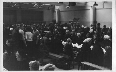 In de kantine van de textielfabriek v.h. Gebr. Driessen in de Dijkstraat worden de nieuwe inwoners van Aalten ontvangen waar zij aanzitten aan de koffietafel. Uit het boek Aalten in Oorlogstijd van J.G. ter Horst