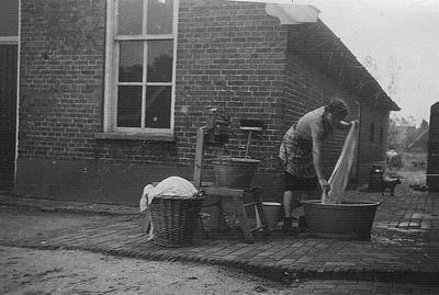 Foto van een wassende vrouw op een erf in Dale in 1942.