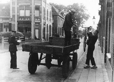 Fietsenvordering in Aalten. Werklieden van de gemeente laden onder toezicht van de politie aan de Bredevoortsestraat in Aalten de eerst gevorderde fiets op een wagen in 1942. Uit het boek Aalten in Oorlogstijd van J.G. ter Horst