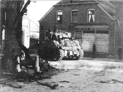 De eerste Engelse tank komt de hoek om bij Schilller Prins op de Haartsestraat in Aalten op 30 maart 1945. Uit het boek Aalten in Oorlogstijd van J.G. ter Horst