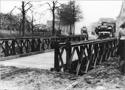 De opgeblazen brug in de Dijkstraat in Aalten werd op 30 maart 1945 snel door een bailly-brug vervangen. Uit het boek Aalten in Oorlogstijd van J.G. ter Horst