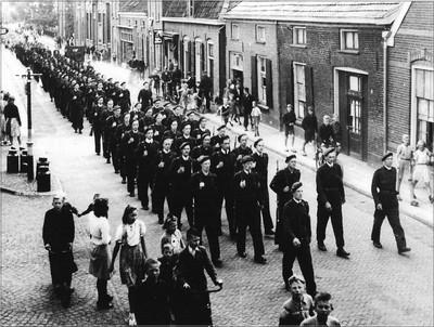 In blauwe overall en met een oranje armband om de linkerarm marcheren Nederlandse vrijwilligers door Aalten. Uit het boek Aalten in Oorlogstijd van J.G. ter Horst