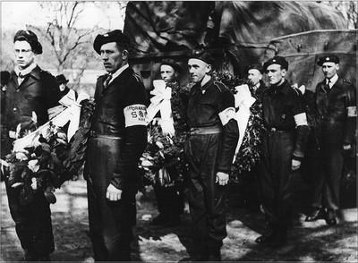 Begrafenis van verzetsstrijder H. Huinink. Leden van de Nedelandse Binnenlandse Stridkrachten droegen kransen naar de begraafplaats. V.l.n.r.: B. van Loenen, Joh. te Lindert, G.W.A. Bulsink, B. te Brinke, B. Bovenkerk, J. Driesten en J. Gringhuis. Uit het boek Aalten in Oorlogstijd van J.G. ter Horst