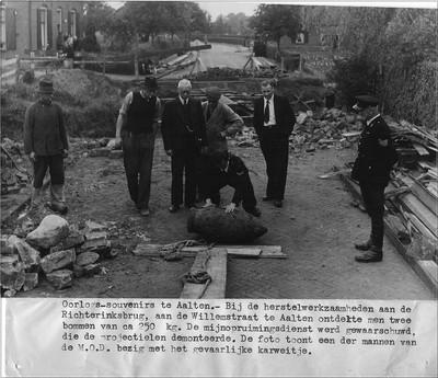 Oorlogs-souvenirs te Aalten.- Bij herstelwerkzaamheden aan de Richterinksbrug, aan de Willemstraat te Aalten ontdekte men twee bommen van ca 250 kg. De mijnopruimingsdienst werd gewaarschuwd, die de projectielen demonteerde. De foto toont een der mannen van de M.O.D. bezig met het gevaarlijke karwei.