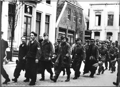 Duitse krijgsgevangenen worden door Nederlandse vrijwilligers over de Markt naar het gevangenkamp begeleid op 30 maart 1945. Uit het boek Aalten in Oorlogstijd van J.G. ter Horst