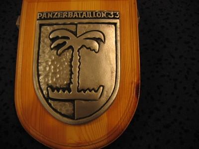 Schildvormige houten ondergrond waarop bevestigd een een metalen zilverkleurig schild, staand verdeeld in twee velden ( linkerveld glad, rechterveld gehamerd) op de scheiding waarvan is afgebeeld een gestileerde palmboom. Het metalen schild is bekroond met de woorden :Panzerbataillon 33
