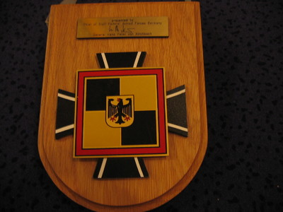 Schildvormige houten ondergrond waarop bevestigd een metalen schild bestaande uit een stapeling van stukken t.w. een zwartkleurig verkort kruis, gedeeltelijk bedekt door een vierkant schaakbordschild (dat is omkaderd door een roodkleurig met gouden banden afgezette lijst ), met vier velden (geel/zwart) dat is beladen met een verkort goudkleurig schild met de afbeelding van een zwarte rood geklauwde en gebekte adelaar. Boven het schild een goukleurig plaatje met de woorden:  presented by/ Chief of Staff Federal armed Forces Germany/ ( onleesbare handtekening)/ General Hans Peter von Kirchbach