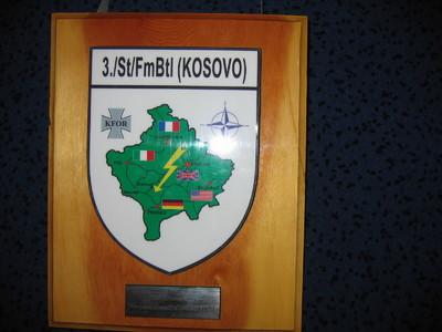rechthoekige houten ondergrond waarop bevestigd een witkleurig metalen schild waarop afgebeeld in groen, een topografische kaart van Kosovo beladen met de vlaggen van Frankrijk, Italie, Groot Britannie, Verenigde Staten en Duitsland. Links van de kaart een verkort kruis met de letters KFOR, rechts van de kaart het symbool van Navo. (i.c vierpuntige ster). Aan de bovenzijde van het metalen schild een kader met inschrift  3./ St/FmBtl (KOSOVO). Onder het metalen schild bevestigd op het hout een zilverkleurig plaatje met inschrift :  Zur Erinnerung/ Fernmeldestaffel ORAHOVAC