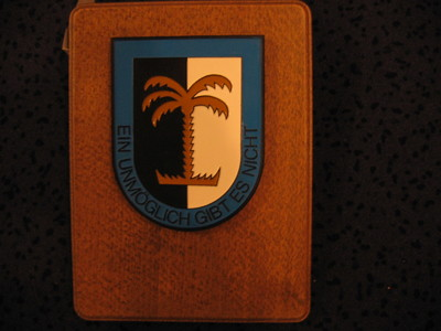 rechthoekige houten ondergrond waarop bevestigd een blauwkleurig metalen schild beladen met een verkort congruent schild. staand verdeeld in een wit en een zwart veld op de scheiding waarvan is afgebeeld een gestileerde palmboom. Onder het verkorte stuk, in het blauwe veld de woorden  EIN UNMÖGLICH GIBT ES NICHT