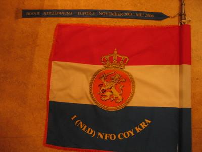 rood-wit-blauwe vlag die langs de drie vrije zijden een oranje band is omboord en voorzien van een donkerblauwe wimpel. Op de witte baan het KL insigne (gekroond oranje medaillon waarop een naar rechts gewende klimmende Nederlandse leeuw, Het medaillon wordt omcirkeld door een parelrand. In de blauwe baan de tekst: 1 (NLD) NFO COY KRA  Op de wimpel de tekst: BOSNIË - HERZEGOVINA EUFOR-3 NOVEMBER 2005- MEI 2006