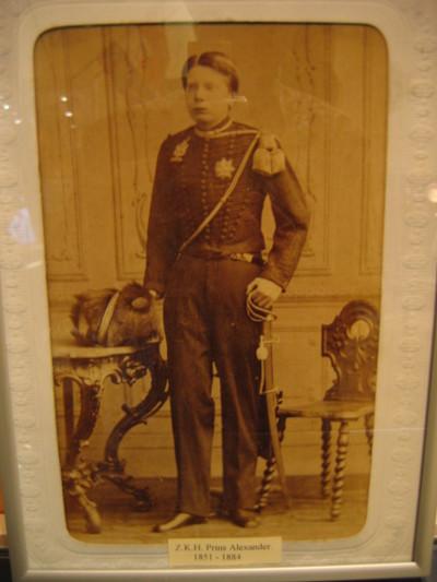 Portret Prins Alexander in kleine tenue officier KRA, hele figuur 3/4 gewend naar rechts in metalen lijst.