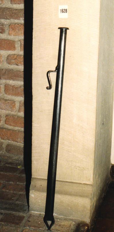 Een holle buis, met aan de bovenzijde een verdikte rand en aan de onderzijde spits toelopen. Aan de zij- en onderkant zijn elegant gevormde dikke metaal draden aangebracht.