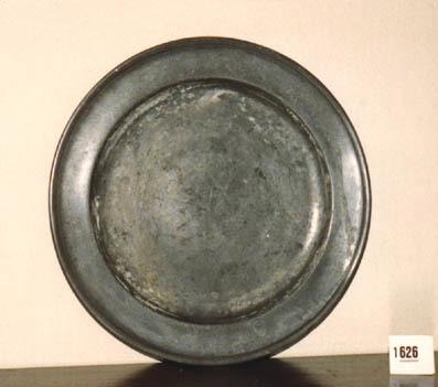 Rond plat bord waarvan de rand verhoogd is en eindigt in een ronde verdikking.