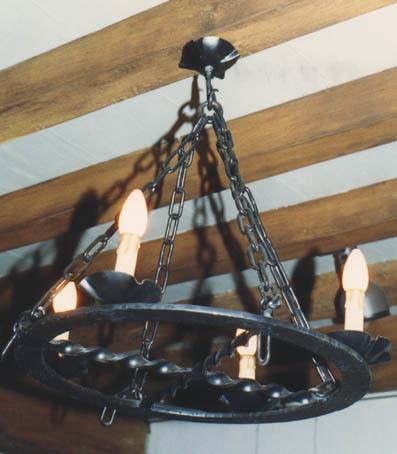 Cirkel vormige metalen ring met in de binnencirkel een kruis van gedraaide stangen. Op de cirkel vier schaaltjes waarop kaarslampjes. Het geheel hangt aan vier bij elkaar komende kettingen.