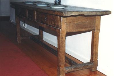 Lange, eikenhouten tafel met overstekend tafelblad en aan de voorzijde twee blinde laden met daar tussen een smalle treklade. Tafel rust op vier poten met vellingkanten op de hoeken, onderling verbonden door een H-vormig kruis van regels.