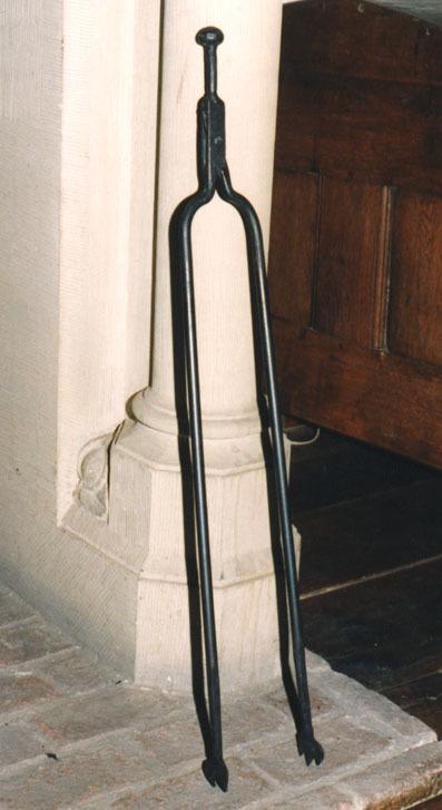 Twee ronden stangen komen aan een zijde samen en zijn daar scharnierend aan elkaar bevestigd. Aan de onderzijde zijn de stangen in rondjes platgeslagen. Een rondje heeft drie tanden de andere twee. Het geheel heeft aan de bovenzijde een ronde knop.