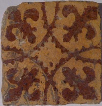 Twee rijen roodaardewerken tegels, gedecoreerd met vier uitgestoken fleur de lismotieven in de hoeken. De achtergrond is opgevuld met witte pijpaarde en de gehele tegel is bedekt met een laagje gele loodglazuur.