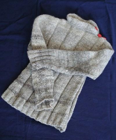 Trui, gemaakt van hondenhaar. Gedurende de oorlogsjaren werd materiaal om kleding te maken steeds schaarser. Men zocht dan ook naar alternatieven. Een voorbeeld daarvan is deze trui. De familie Van Ogtrop woonde in Eemnes. Ze had een donkergrijze Keeshond, die luisterde naar de naam Sten. Bij de overgang van winter- naar zomervacht bleven hele bossen haar in de borstel achter als de hond gekamd werd. Op een dag kwam mevrouw van Ogtrop op het idee de hondenharen opnieuw te gebruiken. Een kennis spon voor haar een groot aantal kluwen wol en daarvan kon zij voor haar kleine dochter Liesbeth een warme trui breien. Liesbeth had, zo lang ze hem kon dragen, de trui graag en vaak aan. Zij herinnert zich dat de trui in het begin verschrikkelijk kriebelde maar lekker warm was. Nu voelt de trui heel fijn en zacht aan.