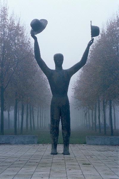 Wie Apeldoorn via het noord-westen verlaat wordt uitgezwaaid door een reusachtige figuur. Wuivend, met in elke hand een hoed, staat hij aan het verkeersknooppunt de Naald, alsof hij door het achterliggende laantje is komen aanlopen. Hij heeft met zijn uitgestrekte armen en zijn rijzige gestalte een uitbundig karakter, maar van dichtbij wekt hij een sobere, bijna melancholische indruk. Henk Visch maakte dit bronzen beeld in opdracht van Stichting Bevrijding '45. Het wuivende gebaar herinnert aan de begroeting van de Canadese bevrijders maar ook aan het afscheid van de gevallenen, vreugde en verdriet tegelijkertijd. In Canada wordt een identiek exemplaar van dit beeld geplaatst - beide figuren groeten elkaar over de oceaan heen. Het staat voor Canada - waarnaar het esdoornblad in het tegelplateau verwijst - en Nederland, voor een nooit meer te vergeten verleden maar ook voor een nieuwe, hoopvolle toekomst. Ondanks zijn grootte is het een intiem beeld. De ruwe, steenachtig gepatineerde huid in combinatie met de ingelegde sprekende ogen geven het beeld een naïef karakter. De tekst op de bronzen plaquette luidt: 'CANADA BRACHT IN NEDERLAND VRIJHEID EN EEN NIEUW LEVEN AAN HET EINDE VAN DE TWEEDE WERELDOORLOG. TUSSEN OKTOBER 1944 EN MEI 1945 VEROVERDE DE CANADESE KRIJGSMACHT, NA HEVIGE GEVECHTEN EN EEN ENORM VERLIES AAN MANSCHAPPEN, DE SCHELDEMONDING EN DE ANTWERPSE HAVEN, DE WEG VRIJMAKEND VOOR BEVOORRADING VAN DE GEALLIEERDEN, VERJOEG DE VIJAND UIT EEN GROOT DEEL VAN HET LAND EN VERSTREKTE VOEDSEL AAN HET DOOR DE NAZI-BEZETTER UITGEHONGERDE NEDERLANDSE VOLK. OP 5 MEI 1945 GAVEN DE DUITSERS ZICH IN WAGENINGEN OVER AAN DE CANADESE LUITENANT-GENERAAL CHARLES FOULKES EN AAN Z.K.H. PRINS BERNHARD DER NEDERLANDEN, BEVELHEBBER VAN DE NEDERLANDSE STRIJDKRACHTEN. DE VRIENDSCHAPSBANDEN DIE TOEN GESMEED WERDEN TUSSEN CANADA EN NEDERLAND HOUDEN TOT OP DE DAG VAN VANDAAG STAND.'