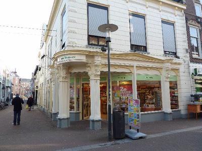 In 1878 opende boek- en kunsthandel Van Tusschenbroek in dit pand (Hoogstraat 30) zijn deuren. De architect was H.A.J. Popping. De puien aan de Hoogstraat en de Nieuwstraat zijn rijk versierd. Mogelijk zijn de vrouwenkoppen uit een modellenboek overgenomen. Het zou ook kunnen dat de architect ze heeft getekend, maar dat is niet bekend.