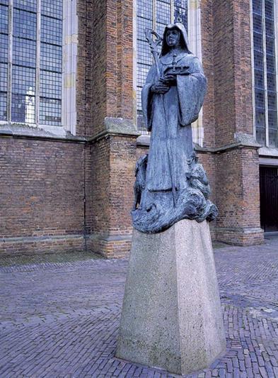 Aan de zuidzijde van de fraaie middeleeuwse Sint Walburgiskerk staat een bronzen beeld van haar patrones en naamgeefster. Deze Engelse abdis uit de achtste eeuw is afgebeeld met een aantal attributen, die alle betrekking hebben op gebeurtenissen tijdens haar leven en na haar dood. Wie de moeite neemt om het beeld heen te lopen, kan zodoende het verhaal van de heilige Walburga als het ware 'lezen'. Al eeuwenlang worden heiligen op deze manier afgebeeld. Waar men vroeger echter de betekenis van de attributen kende, is tegenwoordig de verklarende tekst op de achterkant van de sokkel voor de meesten van ons onontbeerlijk geworden.