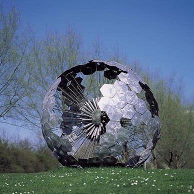 Op een grasveldje in een van de Zutphense zuidwijken lijkt deze zaadbol van een paardebloem min of meer bij toeval te zijn neergestreken, om straks weer te worden meegevoerd met de wind. Zelfs het buitensporig grote formaat van het kunstwerk doet aan deze illusie geen enkele afbreuk. De opengewerkte structuur van 'De parelbloem' verschaft ons verschillende 'doorkijkjes'. Het kunstwerk werd overigens niet speciaal voor deze plaats gemaakt, maar is hier niettemin uitstekend op zijn plaats. De plastiek vormt een natuurlijk element in een groene omgeving.