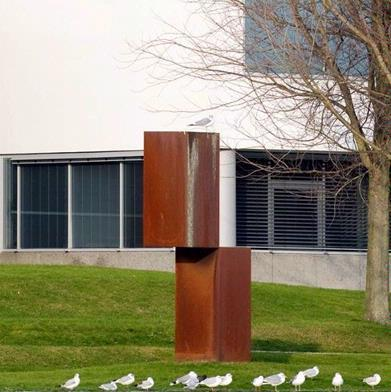 De sculpturen van Lon Pennock bestaan vaak uit dubbelvormen. In dit werk lijken beide identieke stalen blokken elkaar nauwelijks te raken. Voor ons gevoel zou het bovenste blok zelfs naar beneden moeten vallen. De kunstenaar creëert met dit optisch bedrog een zekere spanning, die nog wordt versterkt door de monumentale eenvoud van het ontwerp. Qua vormgeving en concept sluit het beeldhouwwerk aan bij de bekende 'Salami' -reeks, waarmee Carel Visser aan het eind van de jaren '60 furore maakte. De plaats van de sculptuur aan het water, tegen het sobere decor van het nieuwe gerechtsgebouw, is bijzonder goed gekozen.