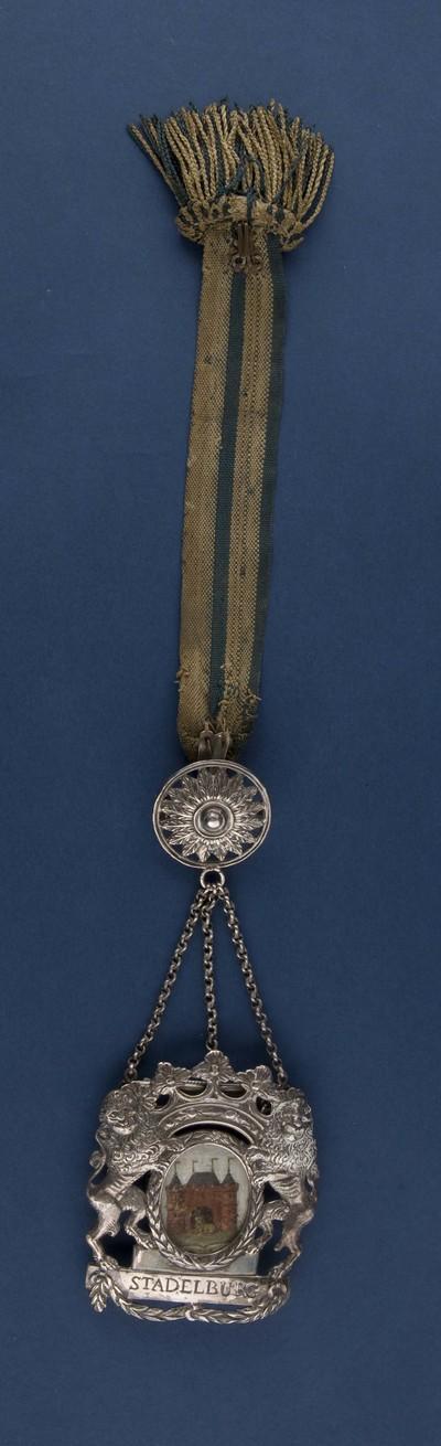 Bodebus van zilver met voorstelling van het stadswapen Elburg, geflankeerd door twee klimmende (aanziende) leeuwen uitgevoerd in zilver, bevestigd aan een draaglint, hangende aan zonnemotief,voorzien van merktekens, destijds gedragen door de stadsbode bij officiele gelegenheden