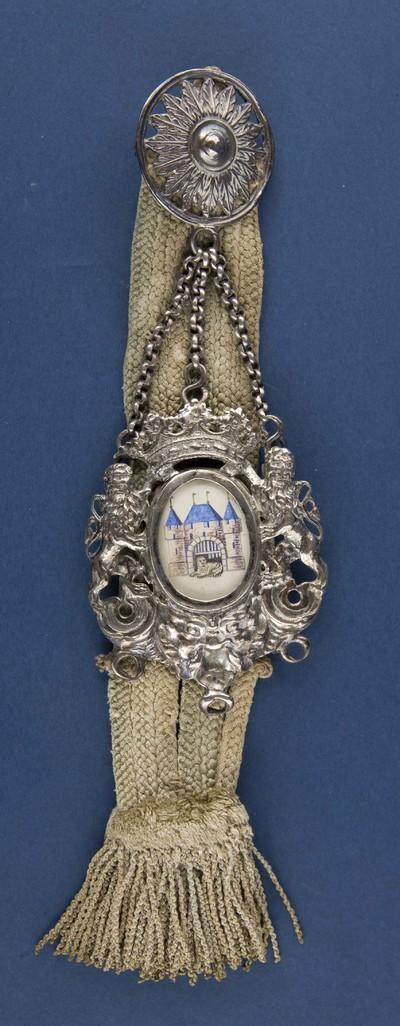 Bodebus van zilver met voorstelling van het stadswapen Elburg, geflankeerd door twee klimmende (aanziende) leeuwen uitgevoerd in zilver, bevestigd aan een lint, merkteken, destijds gedragen door de stadsbode bij officiele gelegenheden
