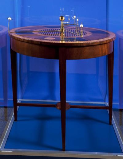 Planetarium op hoge tafel met inlegwerk, van eiken bindhout met mahonie onderstel, blad gefineerd met hulst, ebben, Honduras mahonie en esdoorn, waarop planeetarmen met bolletjes van verschillende grootte om de banen van de planeten om de zon aanschouwelijk te maken