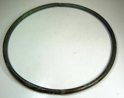 Bronzen halsring, in doorsnede rond en aan de ene zijde versierd met ingeponste kringetjes. De ring is aan één zijde open.