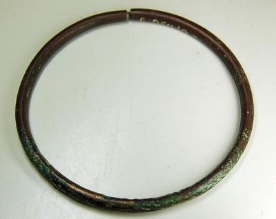 Bronzen halsring, in doorsnede rond, aan één zijde open. Het ene uiteinde is voorzien van een konisch uitsteeksel, dat past in het even ingeboorde andere uiteinde. Kinderhalsketting?