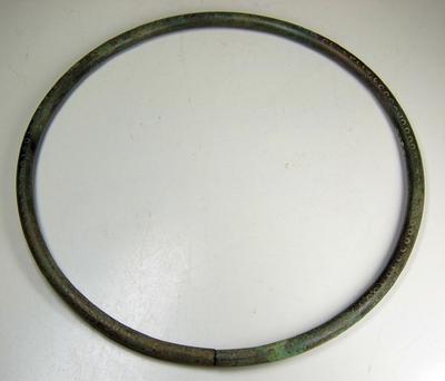 Bronzen halsring, in doorsnede rond, aan één zijde versierd met ingeponste cirkeltjes. De ring is aan één zijde open.