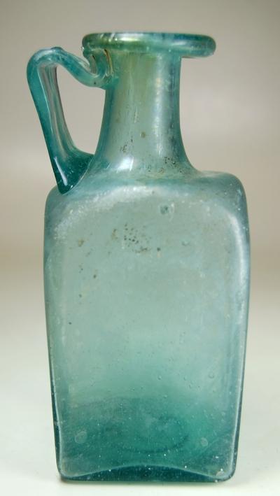 Vierkante glazen fles met een bandvormig oor.