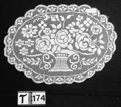 Wit, ovaal, geschulpte rand, in het midden een mand met rozen en andere bloemen.