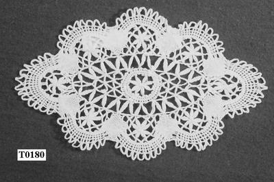 Wit, ovaal,centraal bloem in blaadjes, daaromheen blaadjes en spijltjes.