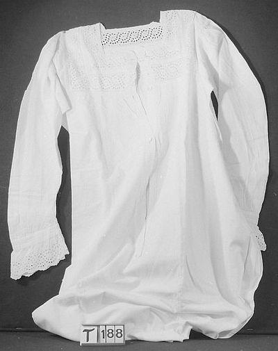 Lang, wit, vierkante hals met dubbele rand broderie en sierbanden op de naden.