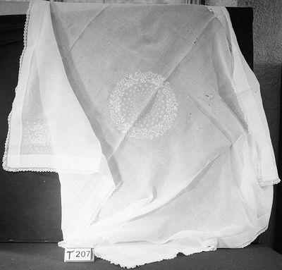 Een wit kleed behorende bij het doopkussen.