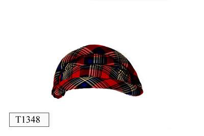 Plat ovaalvormige dameshoed. Rood/blauw/zwart/wit geruite kunstzijde. Opgevulde randen.