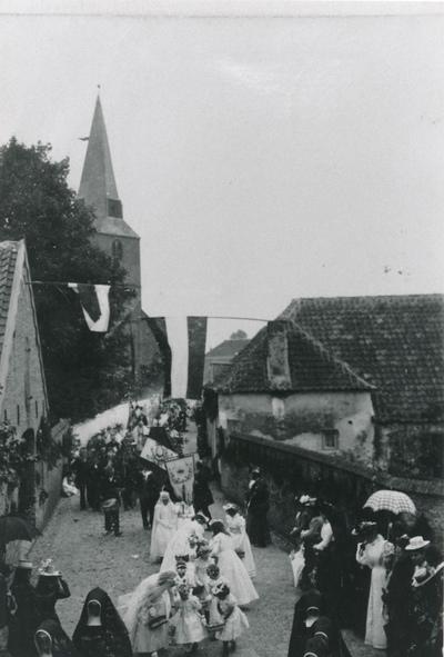 Processie op de hoek van de Langekerkstraat en de Walstraat in het jaar 1902 met Umdrachtbruidjes en dames met grote hoeden en parasols.