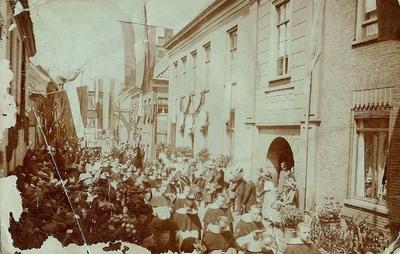 Processie in de Langestraat in 1912 bij de ingang van de gemeenteschool met Dominicanen, veel publiek in een rijk versierde straat